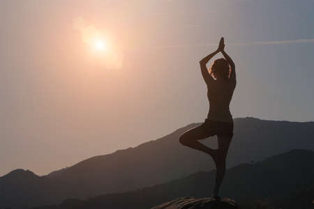 Woman silhouette practicing yoga, mountains and sky background