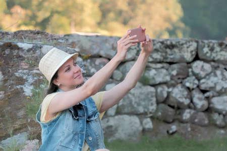 Beautiful smiling caucasian woman in hat taking selfie on smartp