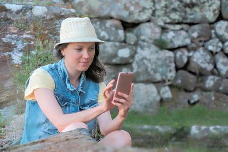 Beautiful caucasian woman in hat using smartphone outdoor