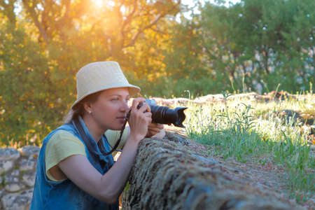 Female photographer taking photo in beautiful countryside
