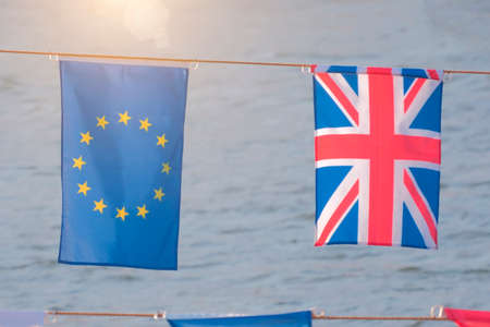 UK and EU flags on cord against water