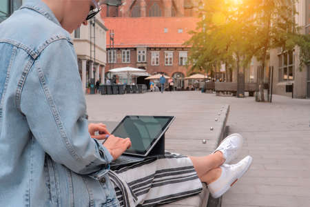 Young womanin in denim jacket sitting and typing on laptop