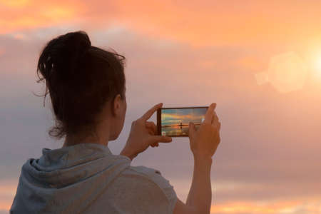 Woman taking photograph of beautiful sunset and coastline on smartphone