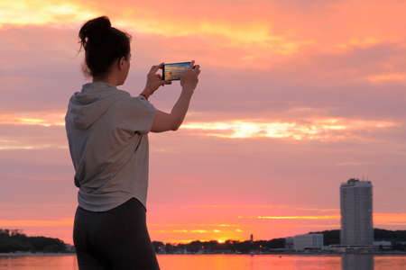 Caucasian woman in sport clothes taking photo on smartphone of sunset Stockfoto