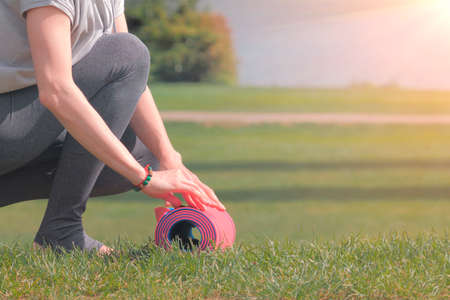 Woman going to practicing yoga, unrolling or rolling her yoga mat on green grass