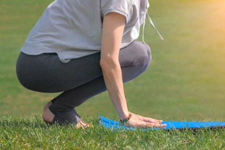 Woman going practicing yoga, preparing for exercise her yoga mat