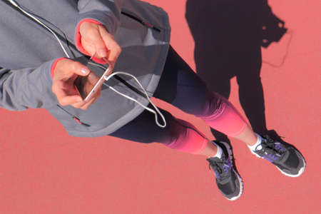 Female athlete in headphones selecting music for training on smartphone