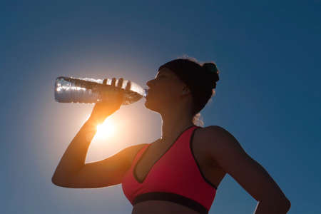 Sport woman drinking water from bottle against the sun