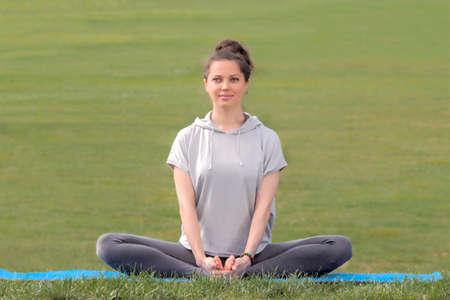 Beautiful caucasian woman sitting in lotus pose
