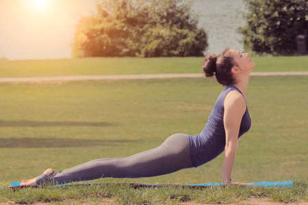 Woman practicing yoga in park on green meadow
