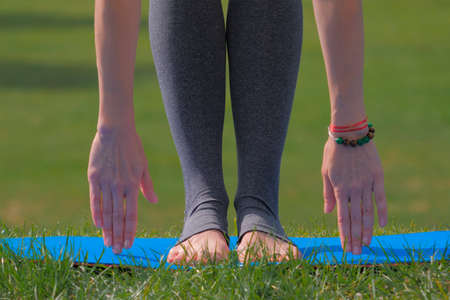 Woman doing sport stretching exercises on green meadow. Sport lifestyle