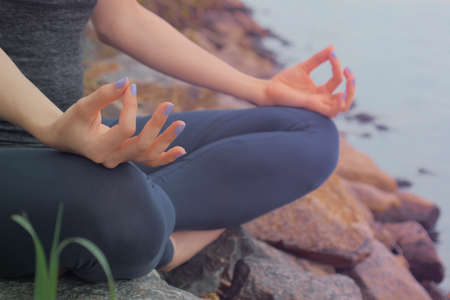 Woman sitting on the rock and meditating in yoga pose