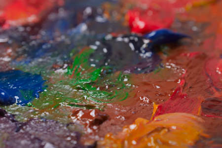 Art multi colored mixed paints on palette. Close up