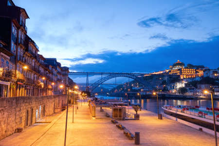Embankment in Old Porto and famous Dom Luis I Bridge in evening.