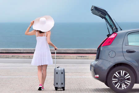Woman with travel bag standing back near hatchback car