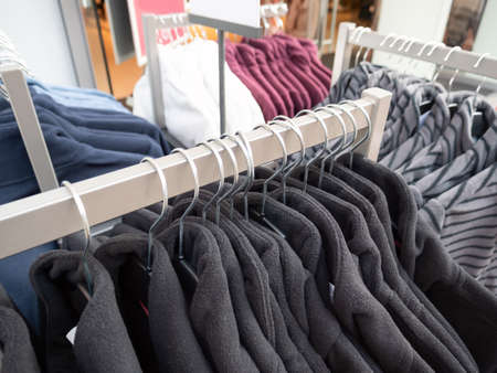 Wear hanging on rack in clothing store. Stockfoto