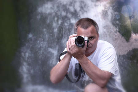 Male Photographer looking at you through camera. Waterfall backg Stockfoto