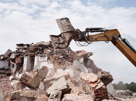Old building demolition concept. Excavator working in rubble.
