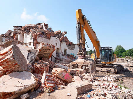 Excavator working in rubble at sunny day. Old building ruins view.