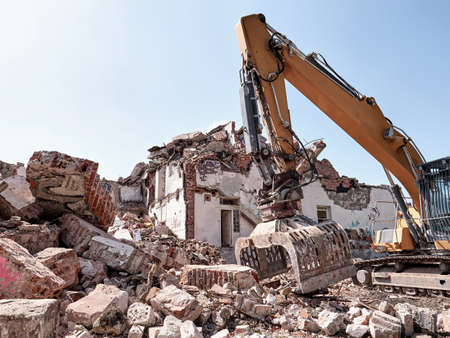 Old house demolition. Excavator working in rubble. Heavy machine at work