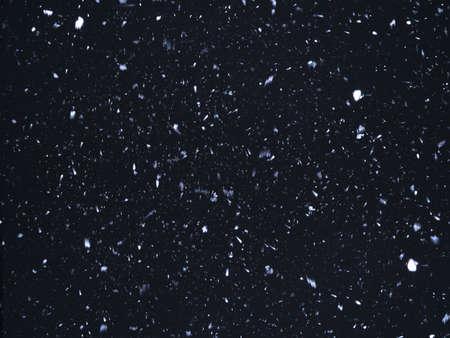 Falling snowflakes. Snow on black background