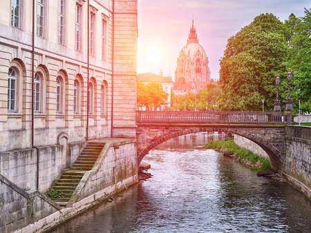 River Leine in Hanover city. City Hall background. View at sunset. Germany Banco de Imagens