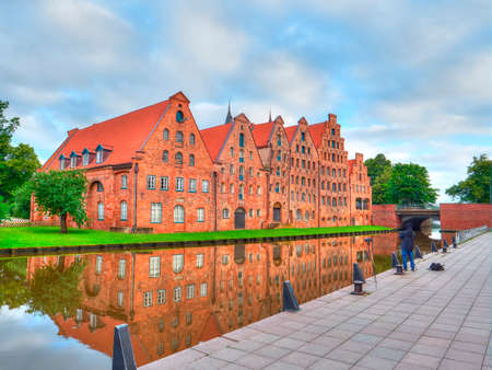 Photographer taking picture of Group Beautiful historic houses on river bank in Lubeck. Germany Stockfoto