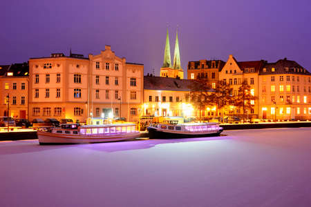 Boats on Frozen Trave river at nights. Lights on Lubeck city emb Stockfoto