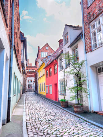 Old Lubeck street with paving stone. Small trees growing in pots. Stockfoto