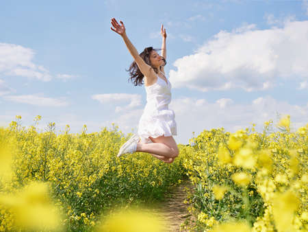 Happy woman jumping with raised hands outdoor.