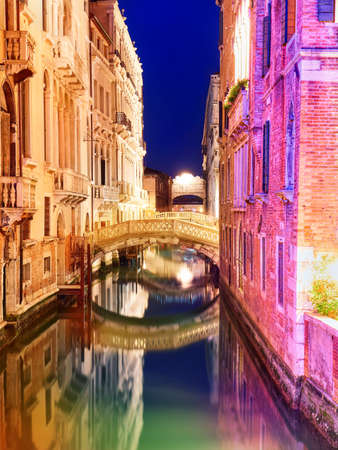 Picturesque canal with bright colorful buildings and little bridge at night with beautiful reflection in water. Venice. Italia