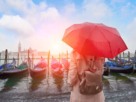 Woman with umbrella standing back and looking on gondolas. San Giorgio Maggiore church background. Venice. Italy Stockfoto