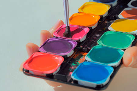Female hands holding art palette with paints and paintbrush Stockfoto - 117132568
