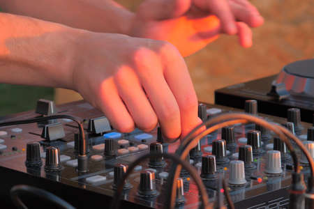 Hand of DJ controlling turntable console mixer. DJ playing music Stockfoto