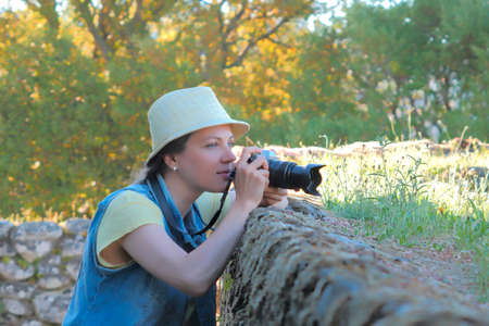 Female photographer working at countryside, shooting photographer Stockfoto - 117132594