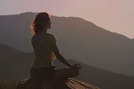 Woman sitting on the rock and meditating in yoga pose. Back view Stockfoto - 117132595