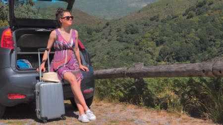 Woman traveler sitting on hatchback car outdoor