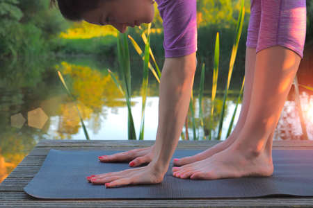 Woman doing stretching exercises on wooden pier at the lake. Stockfoto - 117132605