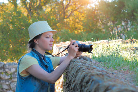 Female photographer taking photo in beautiful countryside. Stockfoto - 117132697
