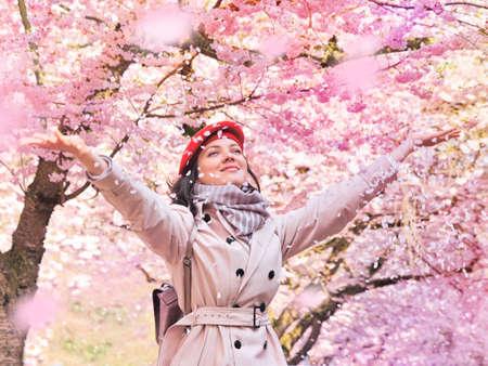 Beautiful woman enjoying a flowering spring garden Stockfoto
