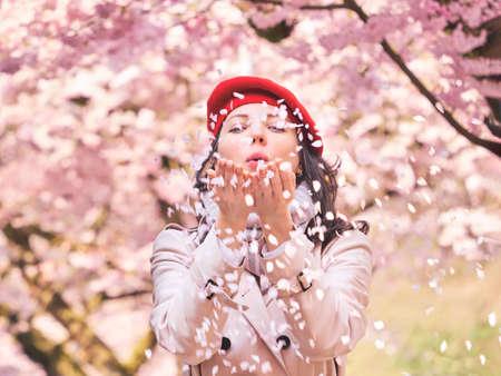 Beautiful Woman blowing petals in her hands, enjoying a flowering spring garden Stockfoto
