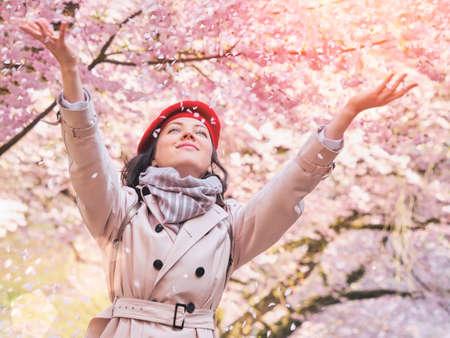 Woman throwing flower petals enjoying spring garden Stockfoto