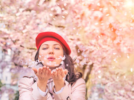 Beautiful Woman blowing petals, enjoying a flowering spring garden Stockfoto - 128888377