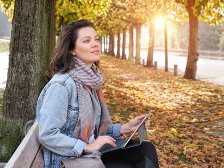 Cute woman with white laptop in the park