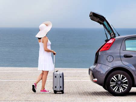 Woman tourist with travel bag standing near hatchback car Stockfoto - 128888382
