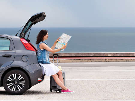 Woman traveler on hatchback car on seaside road. Stockfoto