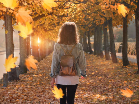 Walking woman in the park, autumn leaf fall