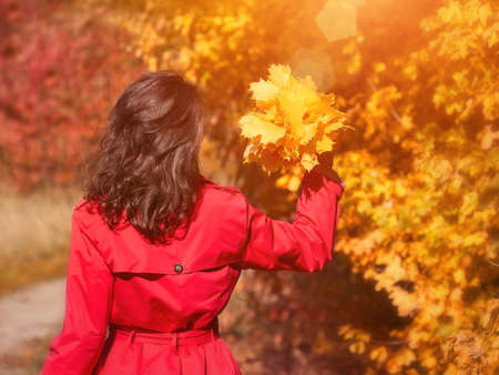 Young beautiful woman enjoying the autumn day with yellow leaves Stockfoto - 131442099