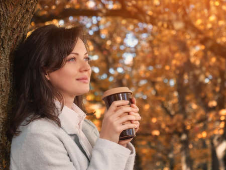 Beautiful woman drinking coffee outdoor enjoying her morning coffee.