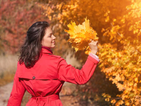 Young woman with yellow leaves in autumn park Stockfoto - 131440979